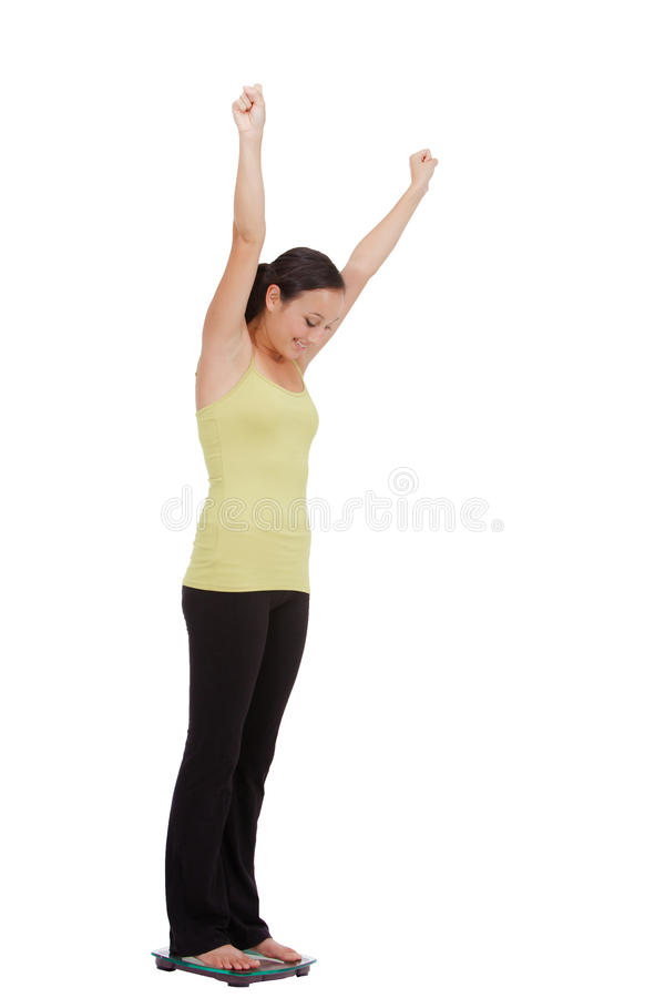 Gewichtsverlust - geeignetes junges Mädchen auf einer wiegenden Skala lizenzfreies stockbild