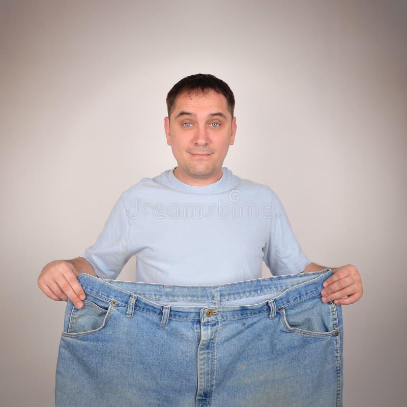 Gewichtsverlust-Mann, der große Hosen hält lizenzfreie stockfotos