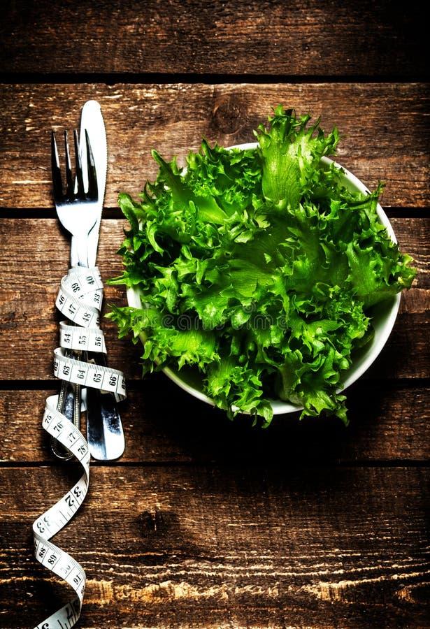 Gewichtsverlust-Salat in einer Schüssel mit messendem Band über hölzernem Vorsprung stockfoto