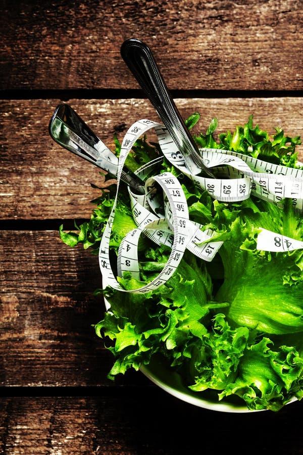 Gewichtsverlust-Salat in einer Schüssel mit messendem Band über hölzernem Vorsprung lizenzfreie stockfotos