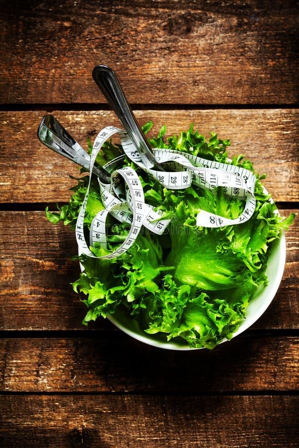 Gewichtsverlust-Salat und messendes Band über hölzernem Hintergrund Di lizenzfreie stockfotografie