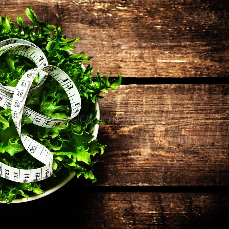 Gewichtsverlust-Salat und messendes Band über hölzernem Hintergrund Di stockbild