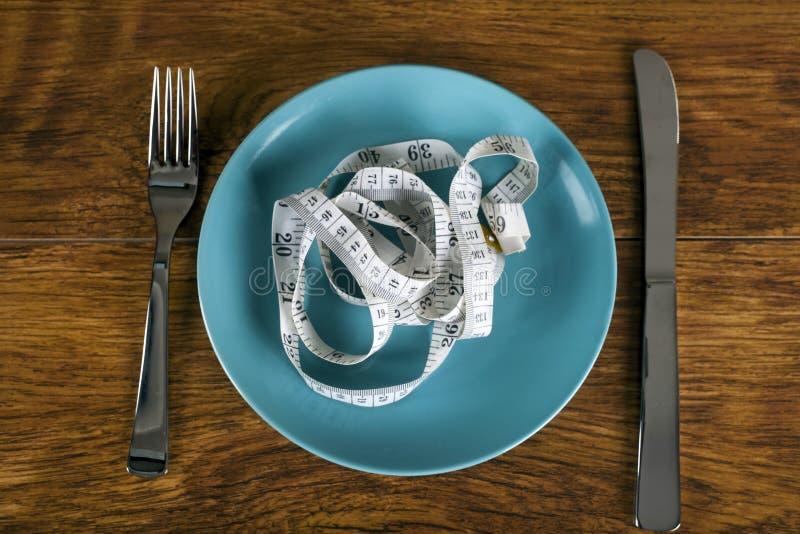 Gewichtsverlustkonzept mit Maßband auf Platte stockfoto