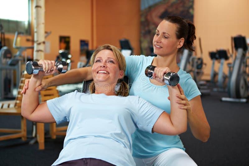Gewichttraining mit Eignungtrainer lizenzfreie stockbilder