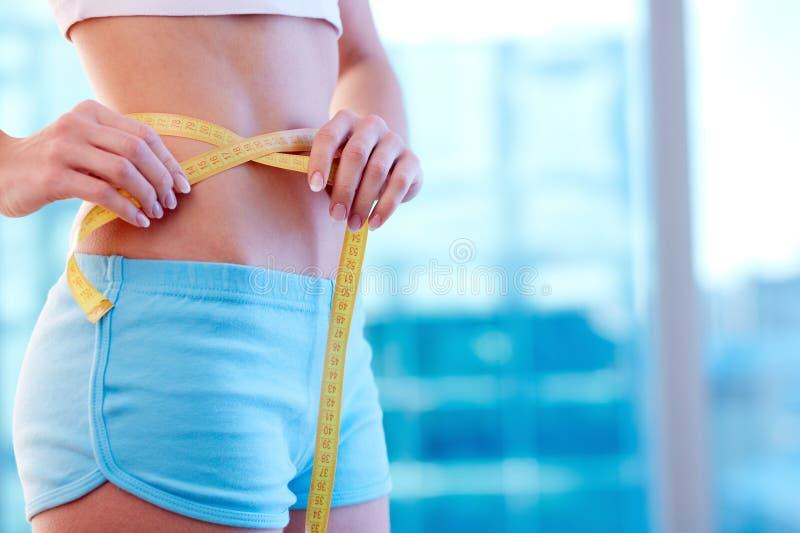 Gewichtverlust Frauentorso mit dem Maß, getrennt auf Weiß stockbilder