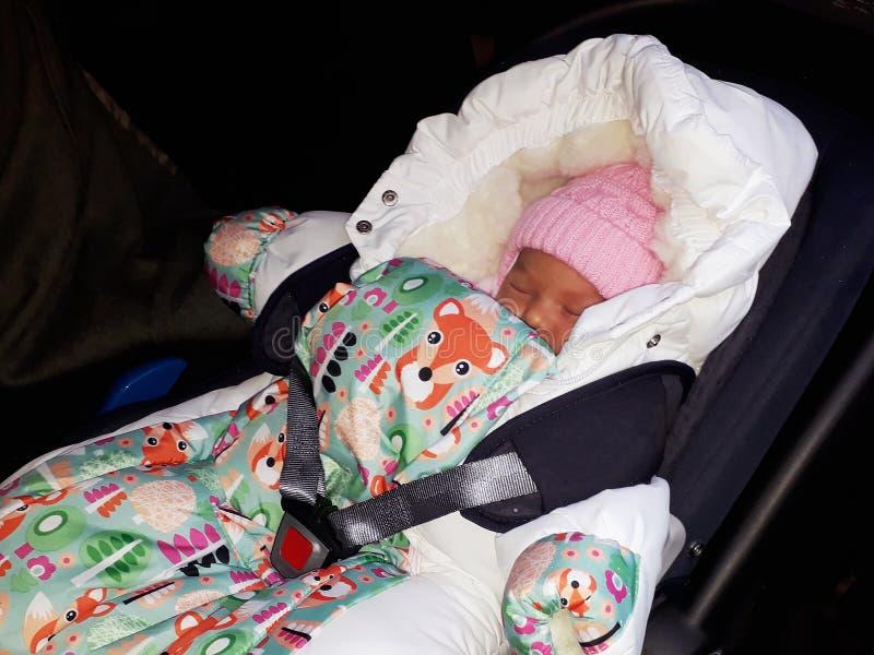 Gewickeltes neugeborenes Mädchen, das im Auto schläft stockfoto