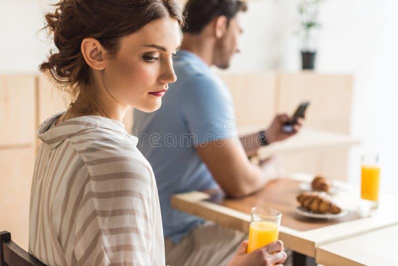 gewijde man die zijn smartphone en ongelukkige vrouwenzitting gebruiken stock foto