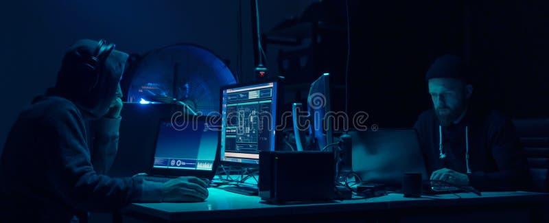 Gewilde hakkers die virus coderen die ransomware laptops en computers met behulp van Cyberaanval, systeem het breken en malware c stock fotografie