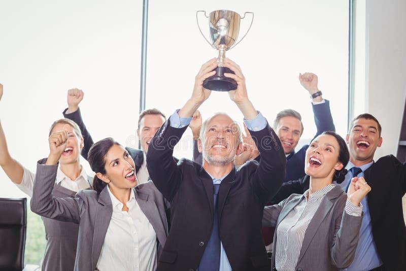 Gewinnendes Geschäft team mit einer haltenen Exekutivtrophäe stockfoto