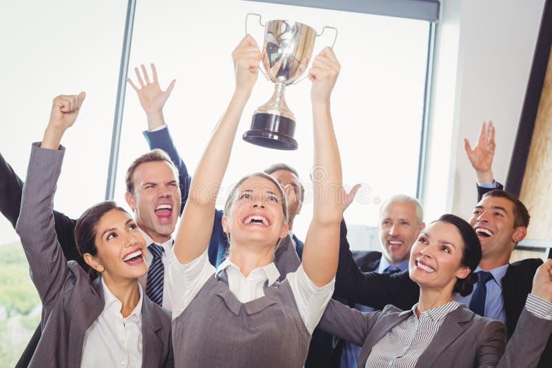 Gewinnendes Geschäft team mit einer haltenen Exekutivtrophäe lizenzfreie stockfotos