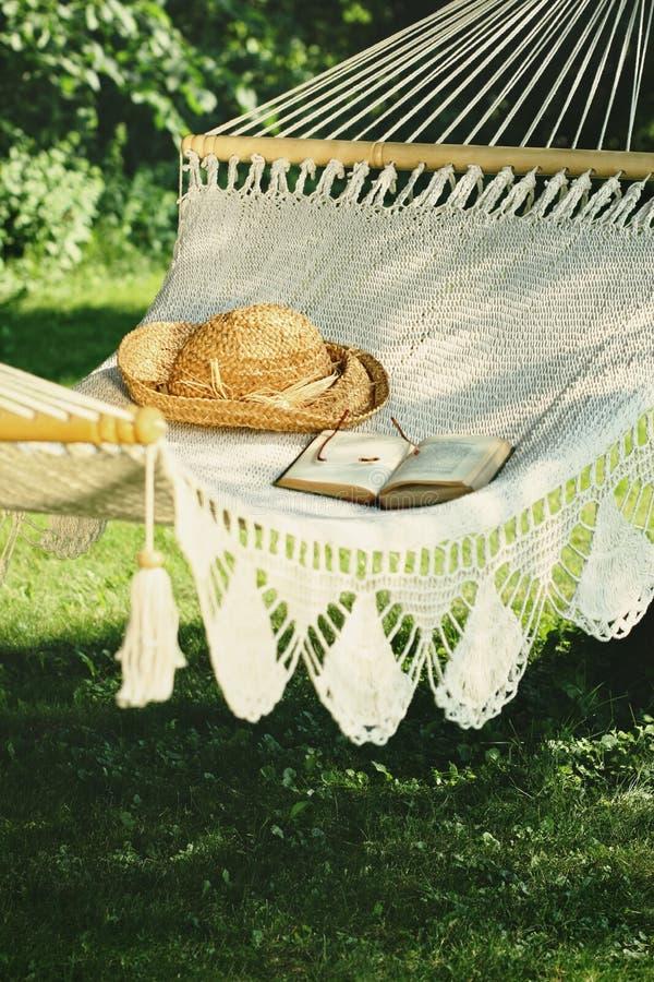 Gewirkte Hängematte mit Hut und Buch stockfotografie