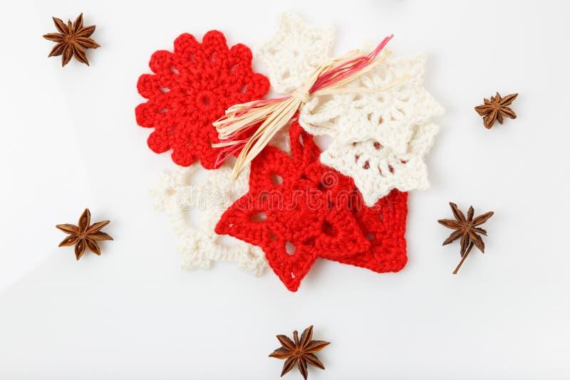 Gewirkte handgemachte weiße und rote Schneeflocken und Sternchen auf einem weißen Hintergrund Weihnachten, Konzept des neuen Jahr stockfotos