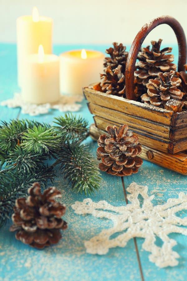 Gewirkte Schneeflocke, Kiefernkegel und brennende Kerzen stockfotografie