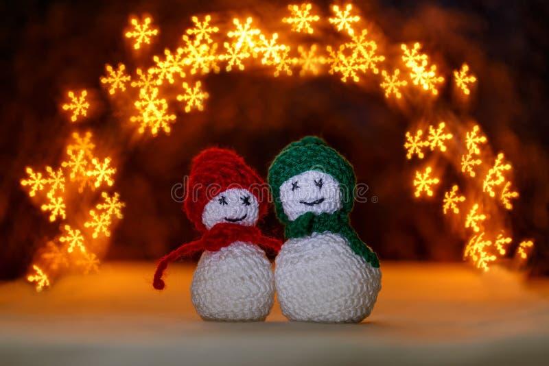 Gewirkte snowmens und bokeh mögen Schneeflocken stockfoto
