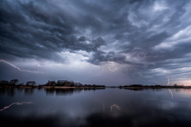 Gewitter über dem See mit Blitzen stockfotos