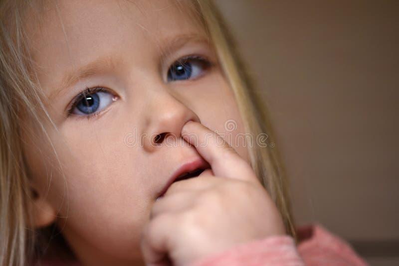 Gewohnheitsmädchen wählt ihre Nase, Finger in der Nase aus stockfoto