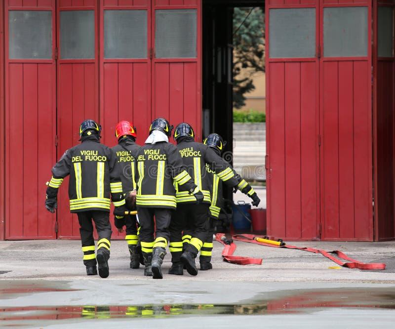 gewonde die persoon door brandbestrijders op een brancard wordt vervoerd stock fotografie