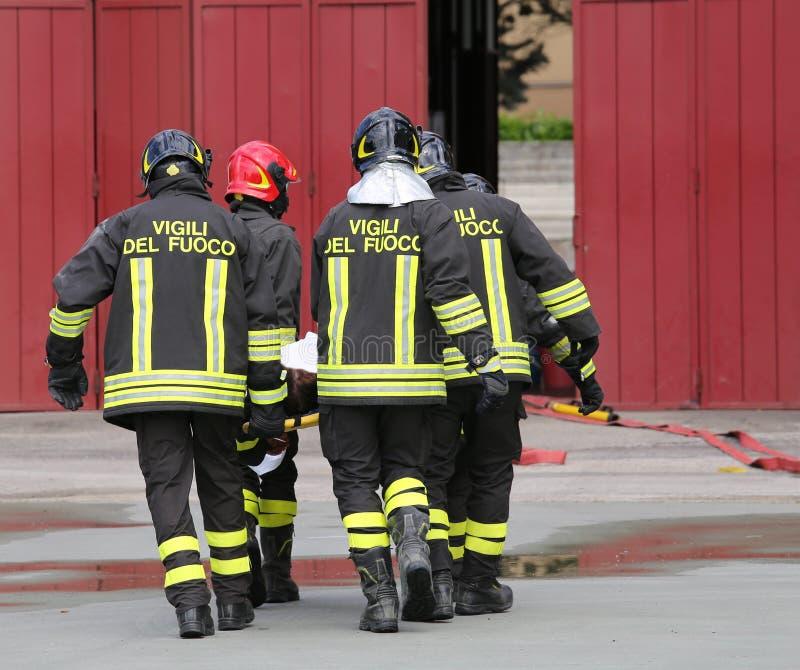 gewonde door brandbestrijders op een brancard wordt vervoerd die stock afbeelding
