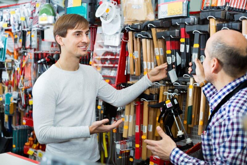 Gewone klant en vriendschappelijke verkoper die hamer kiezen stock foto's