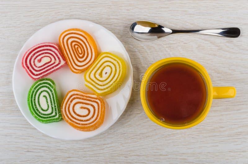 Gewundene Mehrfarbenmarmeladen in der Platte, Tasse Tee, Löffel stockbild