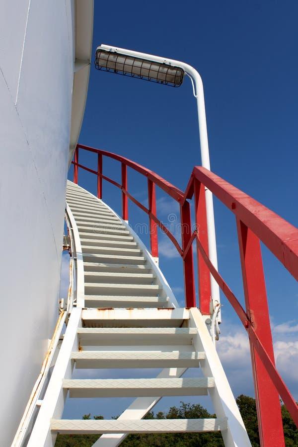 Gewundene Metalltreppe angebracht an der Seite des großen Speichersilos mit rotem Sicherheitszaun und großem Licht auf klarem Hin lizenzfreie stockfotos