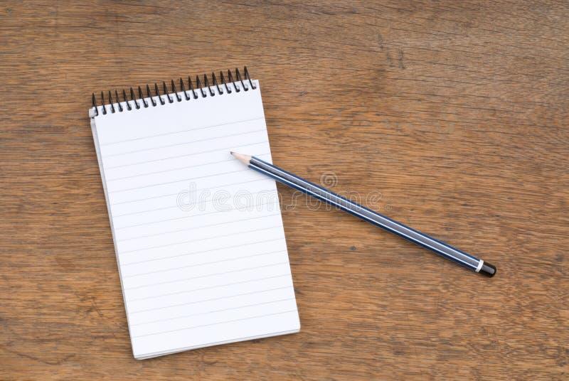 Gewundener Notizblock und Bleistift auf einer hölzernen Tabelle stockbild
