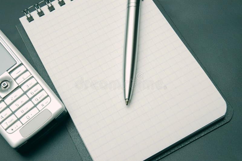 Gewundenes Notizbuch, Feder und Telefone auf dunkelgrauem Hintergrund stockbilder