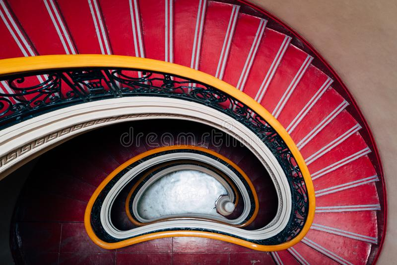 Gewundenes rotes abwärts Treppenhaus stockfotos