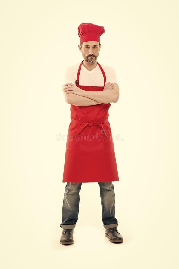 Gewusst f?r sein Kochen B?rtiger reifer Mann im Chefhut und -schutzblech ?lterer Koch mit tragendem Schellfischschutzblech des Ba stockfotos