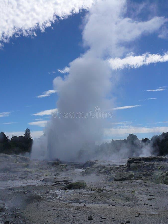 Geyser che fuoriesce vapore contro un contesto di cielo blu e delle nuvole bianche lunghe fotografia stock