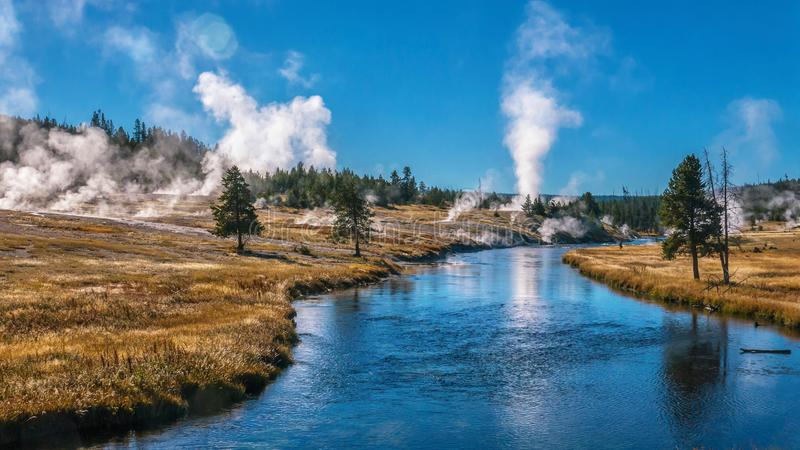 Geyser Steam at Yellowstone National Park. View of the Firehole River flowing through the Upper Geyser Basin of Yellowstone, part of the most active geyser field stock image