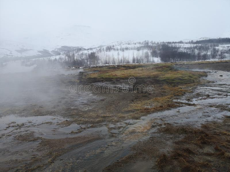 Geysir Strokkur National Park Iceland landscape. Geyser in Strokkur National Park in Geysir,  Iceland. Winter season. Field with snow. Hot water river form by stock images