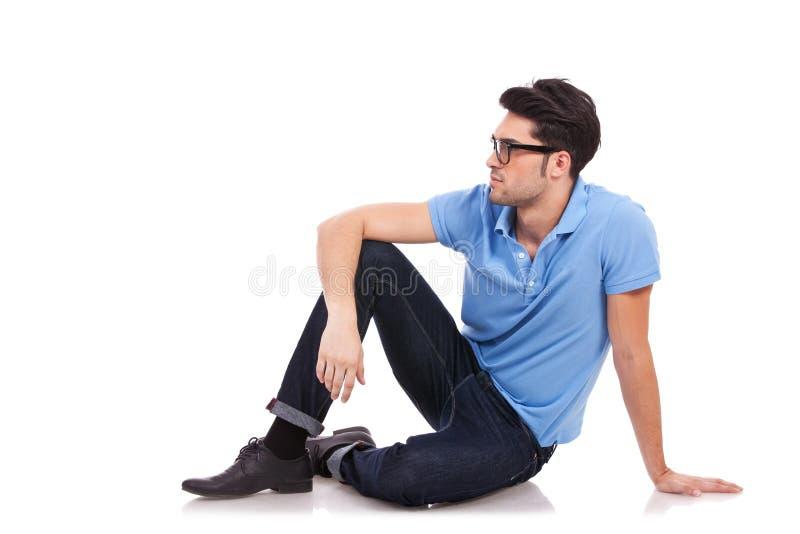 Gezette jonge mens die aan een kant kijkt stock fotografie