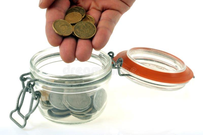 Gezette muntstukken in een glaskruik op een witte achtergrond royalty-vrije stock foto's
