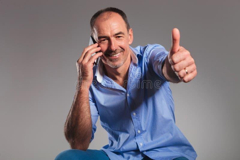 Gezette toevallige hogere mens die op zijn mobiel spreken stock fotografie