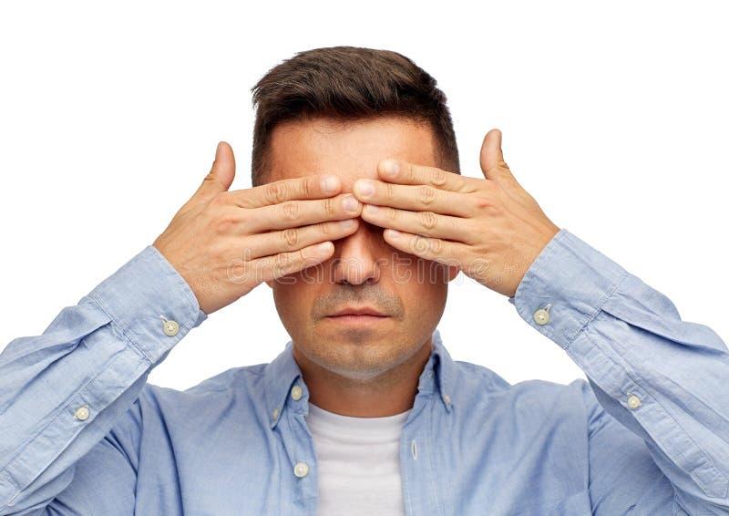 Gezicht die van de mens zijn ogen behandelen met handen stock afbeelding