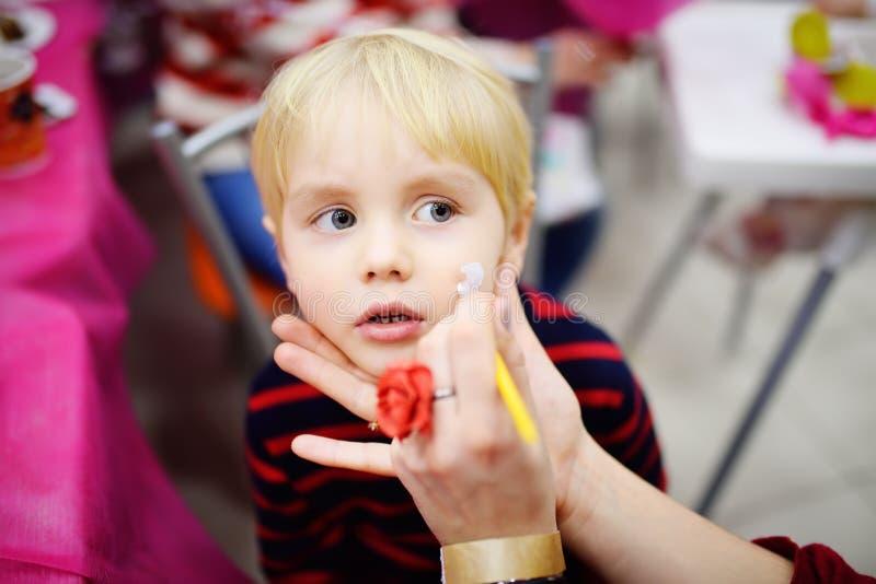 Gezicht die voor leuk weinig jongen schilderen tijdens de partij van de jonge geitjesverjaardag stock fotografie