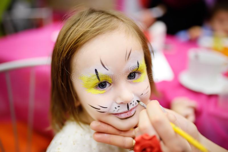 Gezicht het schilderen voor leuk meisje tijdens de partij van de jonge geitjesverjaardag stock foto's