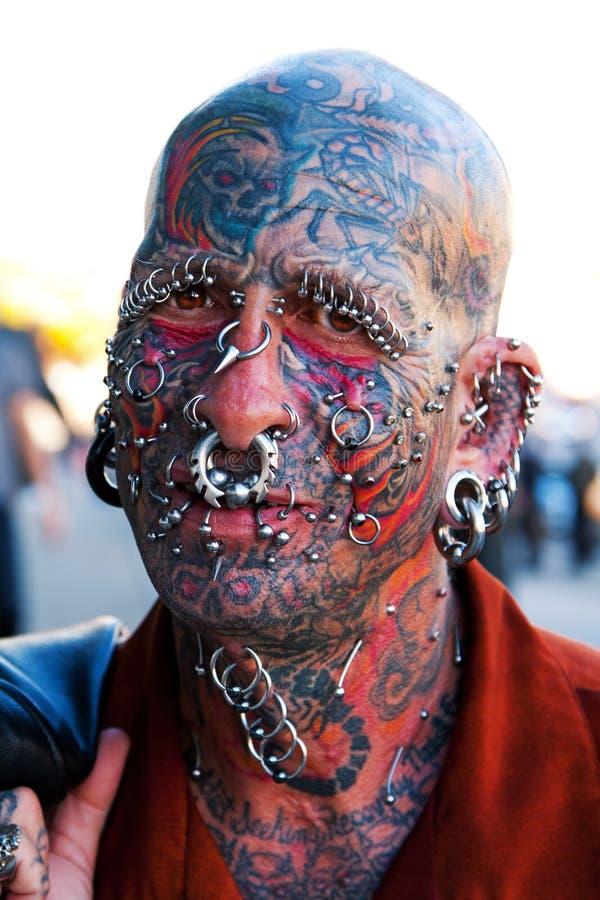 Gezicht met tatoegeringen en het doordringen