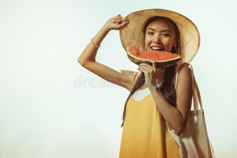 Gezicht-portret van stralende vrolijke vrij jong-volwassen vrouw die de watermeloen eten stock afbeeldingen