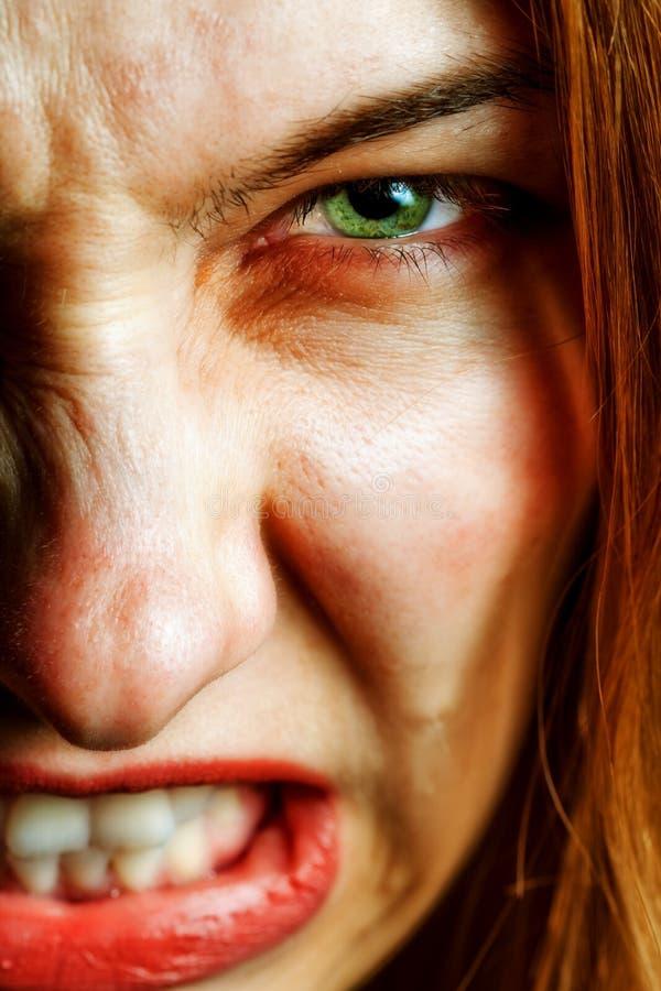 Gezicht van boze vrouw met kwade enge ogen royalty-vrije stock afbeeldingen