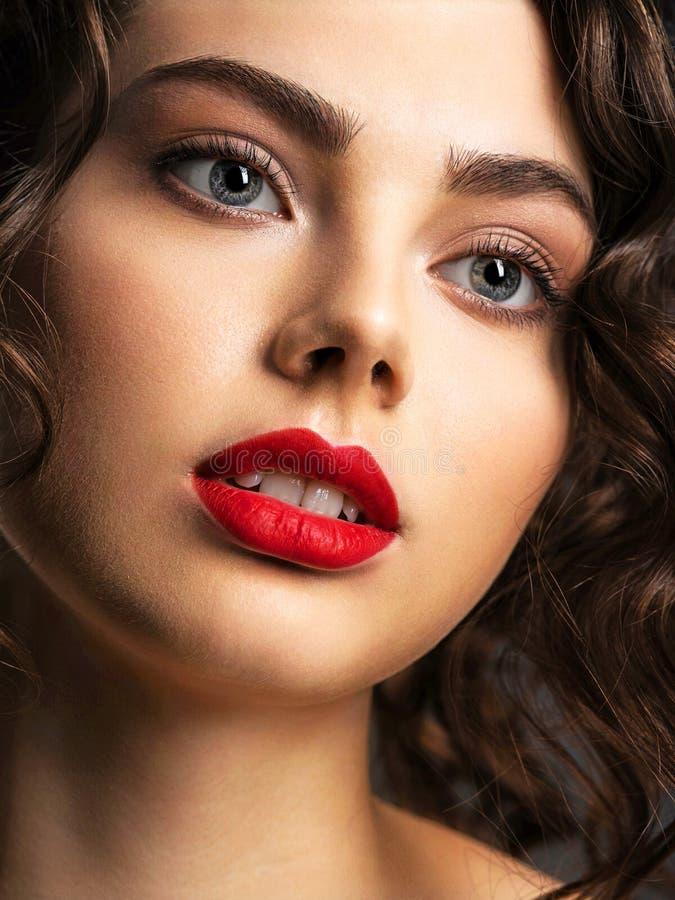 Gezicht van een mooie vrouw met een rokerige oogmake-up en een rode lippenstift royalty-vrije stock afbeeldingen