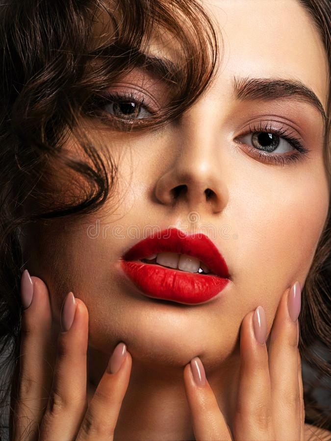 Gezicht van een mooie vrouw met een rokerige oogmake-up en een rode lippenstift stock fotografie
