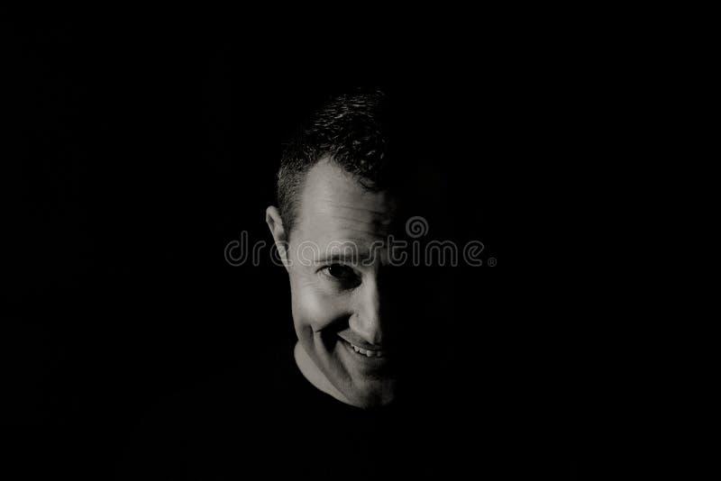 Gezicht van een schuwe glimlachende mens in zwart-wit rustig portret royalty-vrije stock afbeeldingen