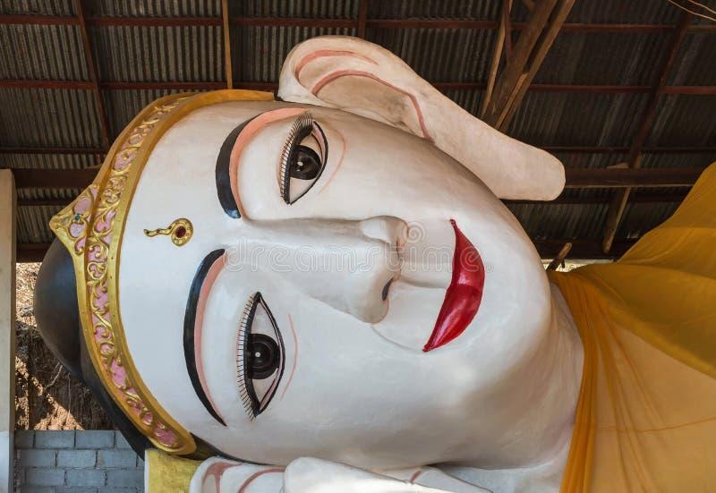 Gezicht van groot wit het doen leunen Boedha rood lippenstandbeeld in myanmar tempel stock afbeeldingen