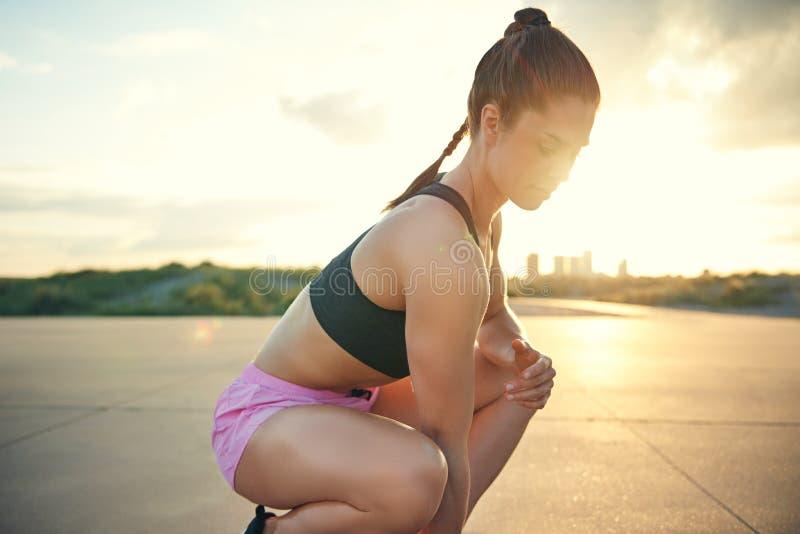 Gezicht van het jonge vrouwelijke atleet hurken dichtbij grond stock fotografie