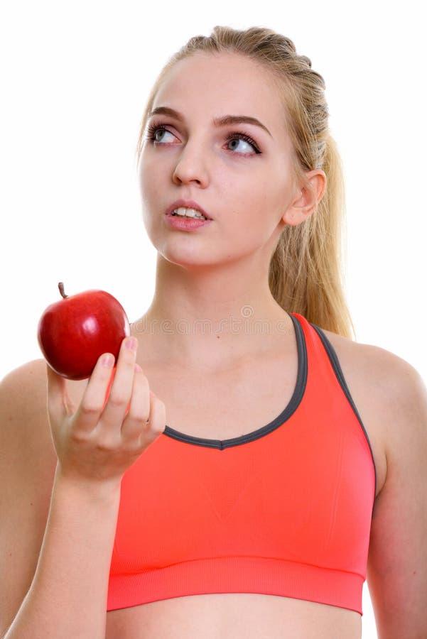 Gezicht van jonge mooie tiener die rode appel houden terwijl thi stock afbeelding