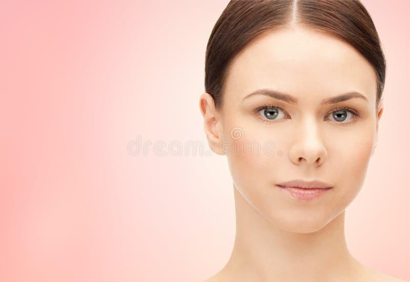 Gezicht van mooie vrouw over roze achtergrond stock fotografie