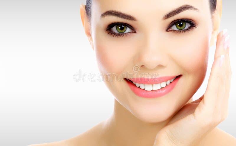 Gezicht van mooie vrouw tegen een grijze achtergrond stock foto's