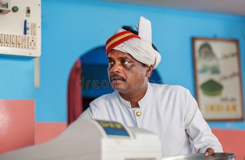 Gezicht van oudere Indische kelner van populaire Indische koffie met kleurrijk binnenland royalty-vrije stock afbeeldingen